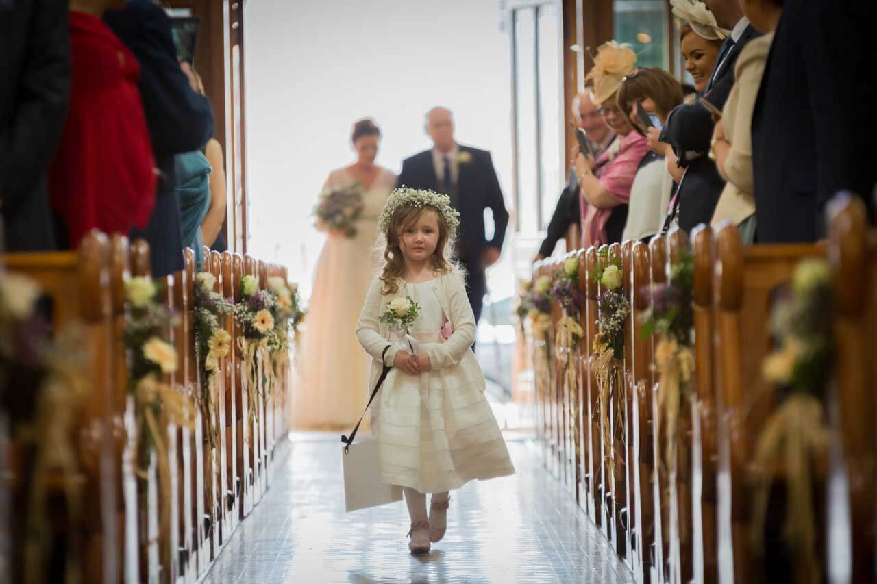 Cute flower girl walking up the aisle